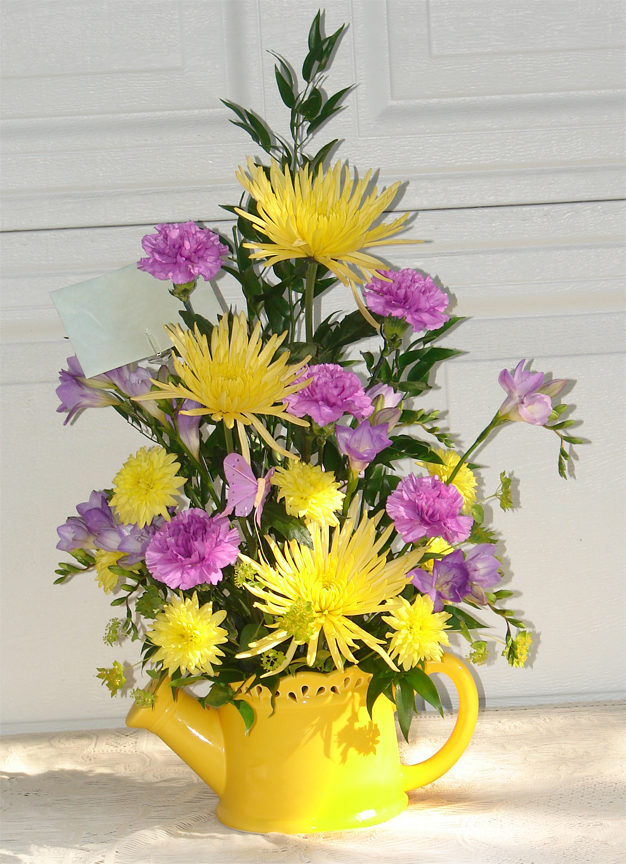 Yellow and pink flowers in yellow watering pot